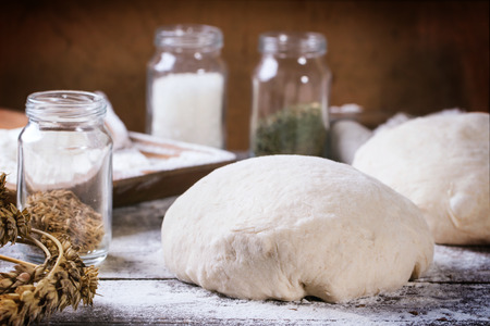 Baking bread. Dough on wooden table with flour, rolling-pin and jars with backing ingredients. photo