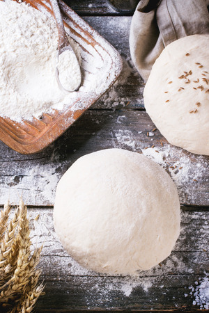 Baking bread. Dough on wooden table with flour, rolling-pin and jars with backing ingredients. Top view photo