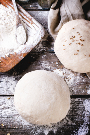 Baking bread. Dough on wooden table with flour, rolling-pin and jars with backing ingredients. Top view. See series