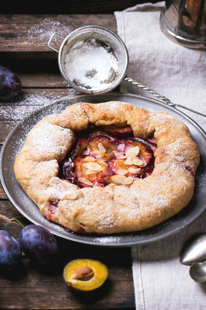 Cake galette with plums, served in vintage metal plate over old wooden table. See series photo