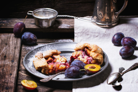 Two pieces of cake galette with plums, served in vintage metal plate over old wooden table. See series photo