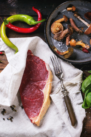 australian beef cow: Raw steak in textile served with vegetables and forest mushrooms over old wooden table