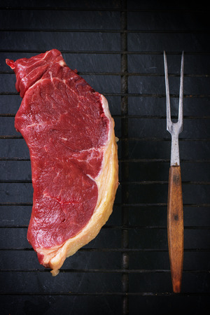 australian beef cow: Raw steak with grill fork on grill Stock Photo