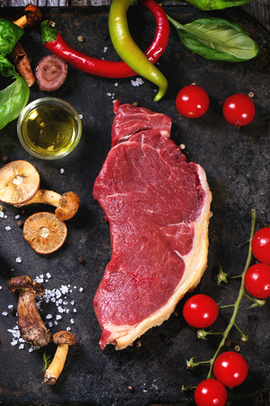 Raw steak served with vegetables and forest mushrooms on black metal cutting board over old wooden table Stock Photo