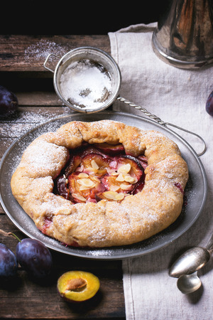Cake galette with plums, served in vintage metal plate over old wooden table photo