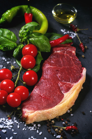 australian beef cow: Raw steak with vegetables over black stone