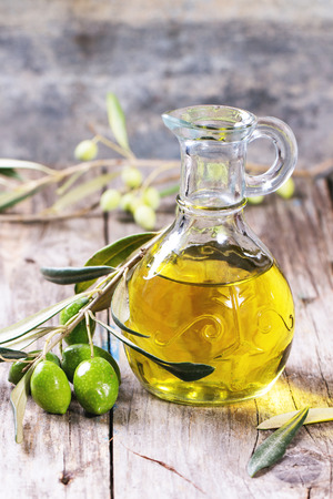 extra: Battle of olive oil with olive branch over wooden table. Stock Photo
