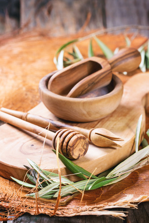 Olive wood kitchen utensil with green olive branch over wooden table. See series. photo