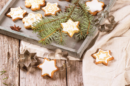 Assorted of Christmas cookies on wooden tray, served with Christmas tree branch over old table photo