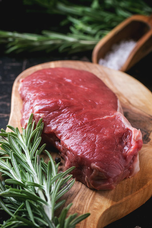 australian beef cow: Raw steak on olive cutting board with rosemary herbs and red hot pepper over black wooden table. See series