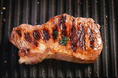 australian beef cow: Grilled steak with butter sauce over black grill Stock Photo