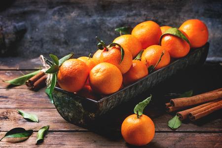 frutas tropicales: Mandarinas con las hojas y la rama de canela en la mesa de madera vieja. Foto de archivo