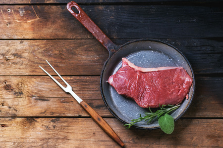 australian beef cow: Raw steak in vintagev pan over old wooden table. Top view. Stock Photo
