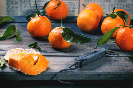 steelyard: Tangerines with leaves and vintage steelyard on old wooden table. Stock Photo
