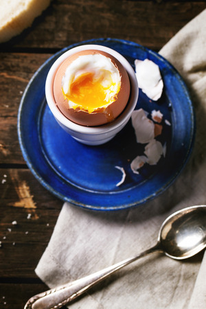 eggcup: Breakfast with soft-boiled egg, served with bread over old wooden table. Top view.