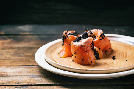 Salmon rolls with black caviar, served on ceramic plate on old wooden table. Stock Photo
