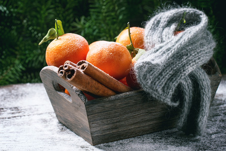 Wooden basket with tangerines, cinnamon sticks and scarf over wooden background with snow and cone. photo