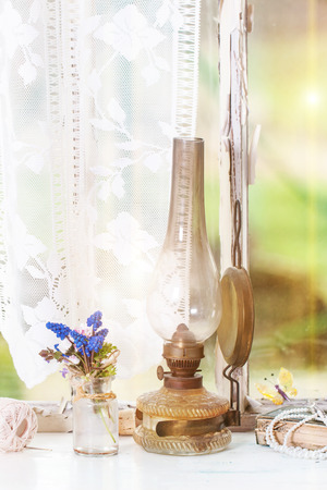 oil lamp: Fragment of interior on old windowsill with vintage lamp, book and wildflowers