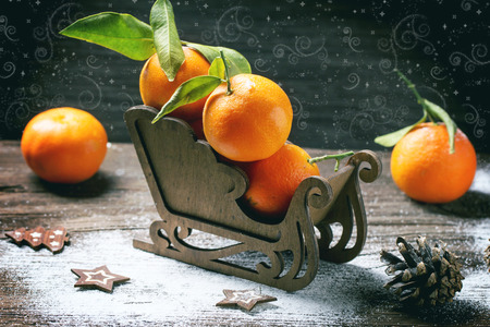 Wooden toy sled with tangerines over wooden background with snow and cone. photo