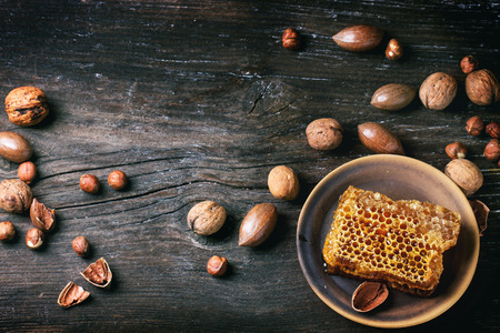 Honeycomb on ceramic plate and mix of nuts over old wooden table. Top view. See series