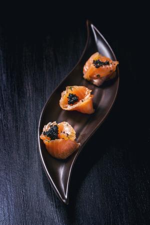 Platte der Lachse rollt mit schwarzem Kaviar über schwarzer strukturierter Oberfläche Standard-Bild - 34268765