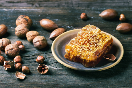 Honeycomb on ceramic plate and mix of nuts over old wooden table. See series photo