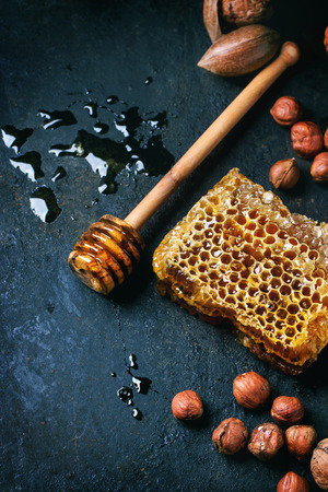 Honeycomb with honey dipper and mix of nuts over black surface. Top view. See series photo