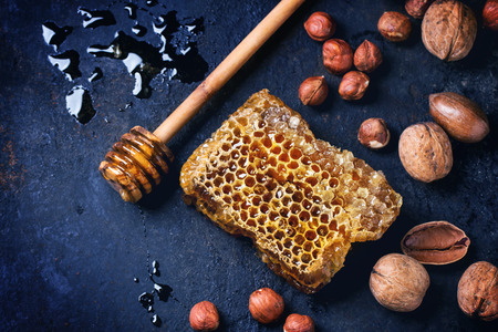 Honeycomb with honey dipper and mix of nuts over dark blue surface. Top view. See series photo