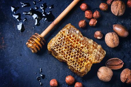 Honingraat met honing dipper en mix van noten over donker blauwe ondergrond. Bovenaanzicht. Zie serie