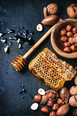 Honingraat met honing dipper en mix van noten op een zwarte ondergrond. Bovenaanzicht. Zie serie
