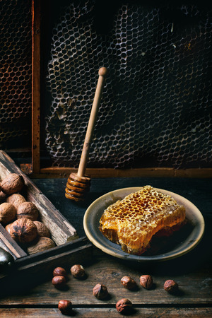Fresh honeycomb with mix of nuts over old wooden table. See series photo