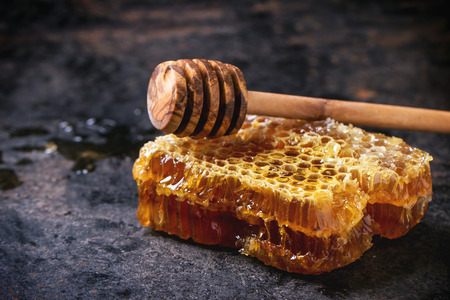 Honeycomb with honey dipper over black surface