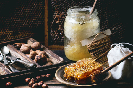Fresh honeycomb with jar of old honey and mix of nuts over old wooden table. See series photo