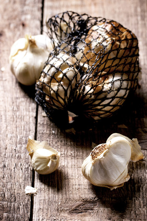Mesh bag of smoked garlic over wooden background. See series photo