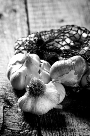 Mesh bag of smoked garlic over wooden background. In black and white photo