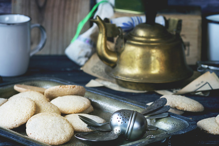bisquit: Almond cookies served with vintage teapot over old wooden table