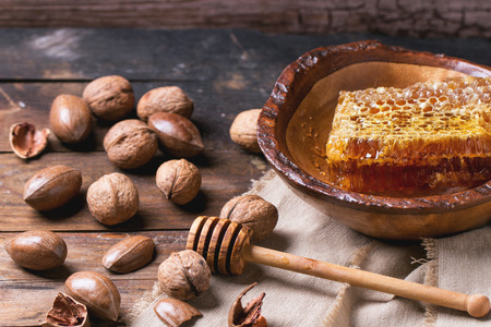 Honeycomb in wooden bowl and mix of nuts over old wooden table.  photo