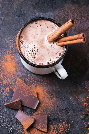 Taza de la vendimia de chocolate caliente con palos de canela sobre fondo oscuro