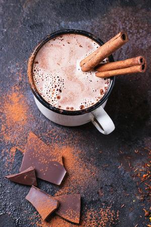 Weinlese-Tasse heißer Schokolade mit Zimtstangen auf einem dunklen Hintergrund