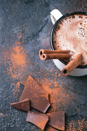 Vintage mug of hot chocolate with cinnamon sticks over dark background. Top view. Foto de archivo