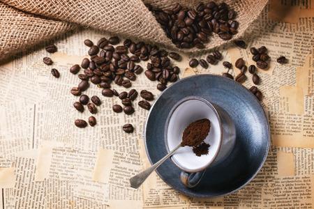 oude krant: Blauwe keramische cup met gemalen koffie en gebrande koffie bonen op oude krant. Bovenaanzicht.