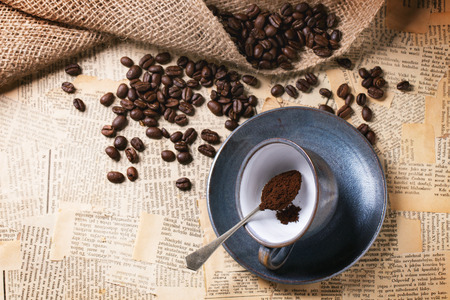 old newspaper: Blue ceramic cup with ground coffee and roasted coffe beans over old newspaper. Top view.