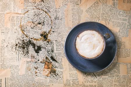oude krant: Blue keramische kopje cappuccino over oude krant. Bovenaanzicht.