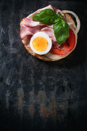 toasted sandwich: Sandwich with ham, eggs, vegetables and ketchup over black metal background. Top view