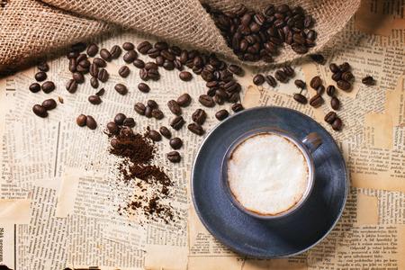 oude krant: Blauw keramiek kopje cappuccino met gebrande koffiebonen over oude krant. Bovenaanzicht.