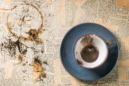 old newspaper: Blue ceramic cup of coffee grounds over old newspaper. Top view.