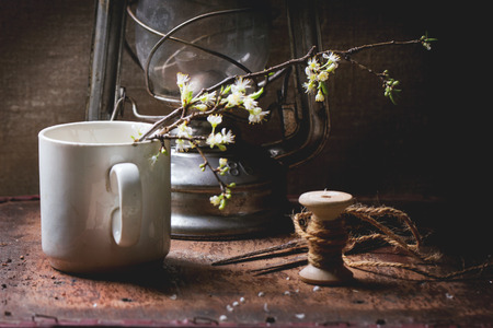 Vintage still-life with blossom branch of apple tree in old ceramic mug, scissors, reel and old oil lamp over brown wooden surface. photo