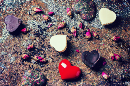 tea filter: Chocolate candies heart shaped with dry tea roses at stone background for Valentines Day. With retro filter effect