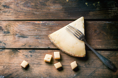 Big piece and little cubes of Belgian cheese with vintage fork over wooden background. Top view. Standard-Bild