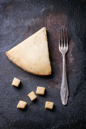 Big piece and little cubes of Belgian cheese with vintage fork over black background. Top view.